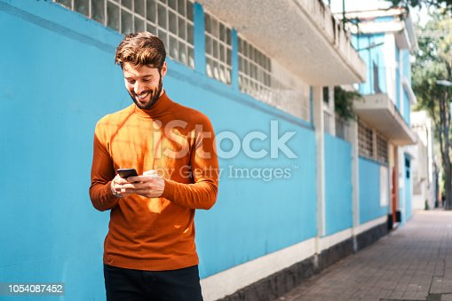 Smiling man walking by the colorful wall while using mobile phone