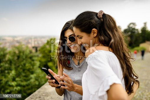 Two tourist women using mobile phone at the nature