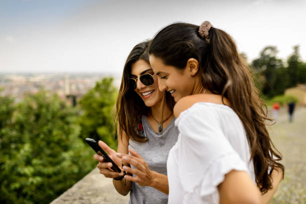 Using mobile phone. Two tourist women using mobile phone at the nature latin american culture stock pictures, royalty-free photos & images