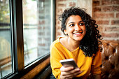 Young Indian woman using mobile phone at the bar