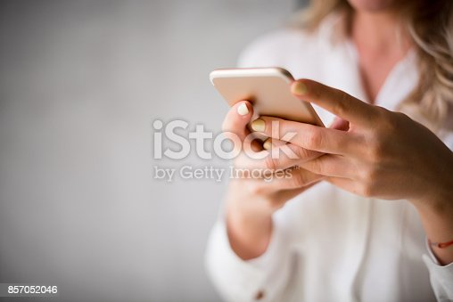 Close up of a woman using her smartphone indoors.