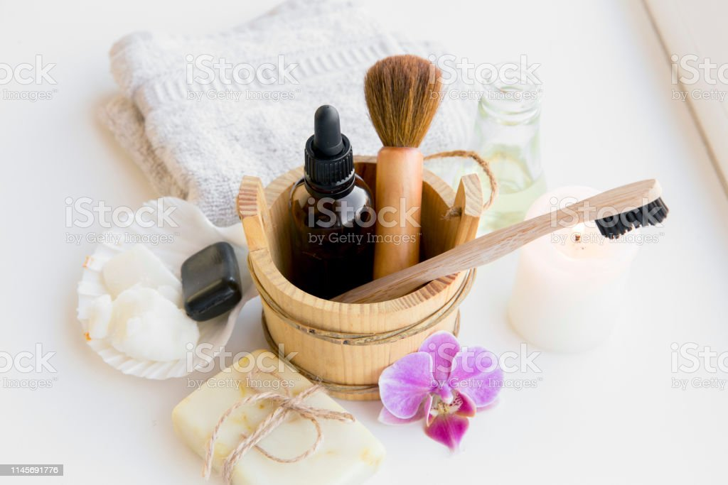 Using natural material products in home, different cosmetic products in bathroom. Minimizing ecological footprint concept. Bamboo bath towel, biodegradable bamboo toothbrush, clay mask, coconut oil. - Foto stock royalty-free di Accudire