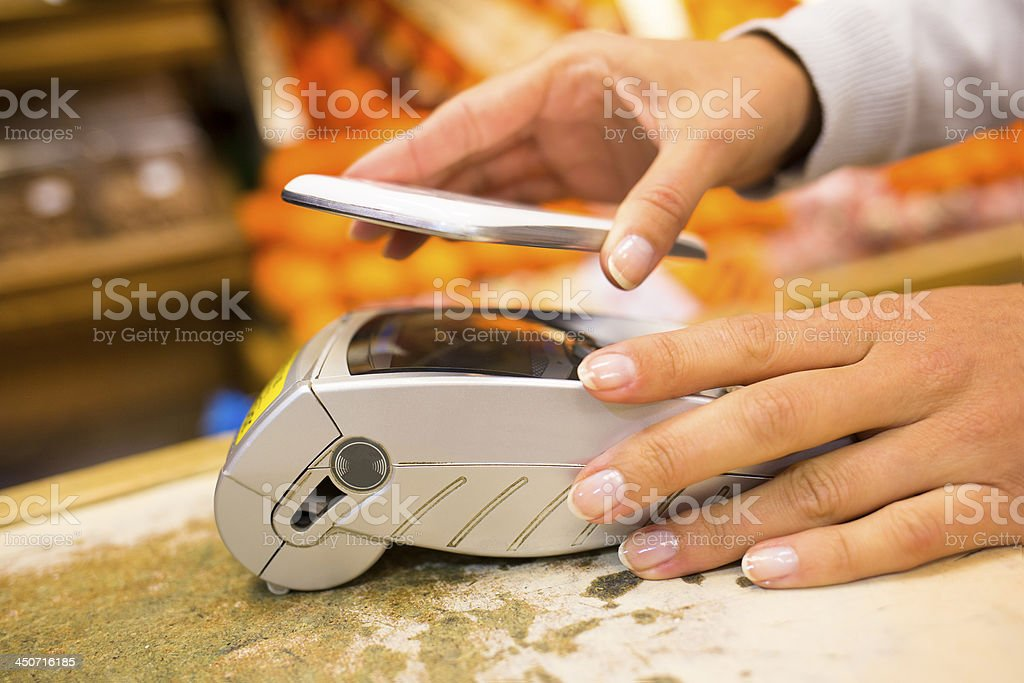 Using NFC enabled smart phone at pay terminal royalty-free stock photo