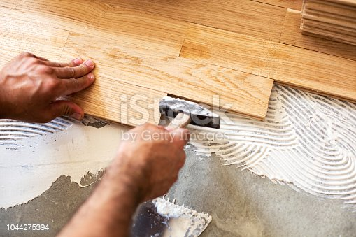 922081754istockphoto Using of hammer for parquet alignment 1044275394