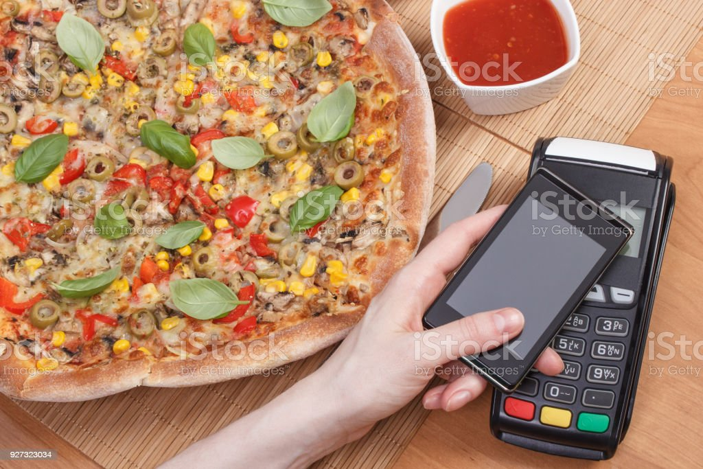 Using payment terminal and mobile phone with NFC technology for paying in restaurant for vegetarian pizza stock photo
