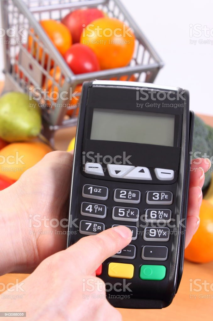 Using payment terminal, fruits and vegetables, cashless paying for shopping, enter personal identification number stock photo