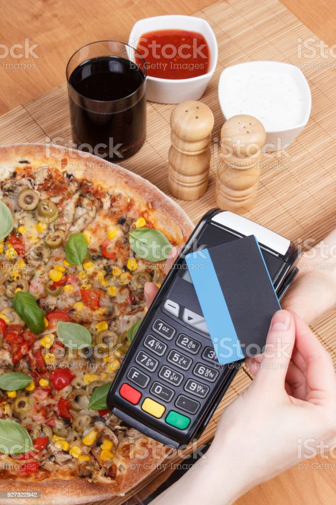 Using payment terminal with contactless credit card for paying in restaurant stock photo