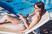 Using phone by the swimming pool