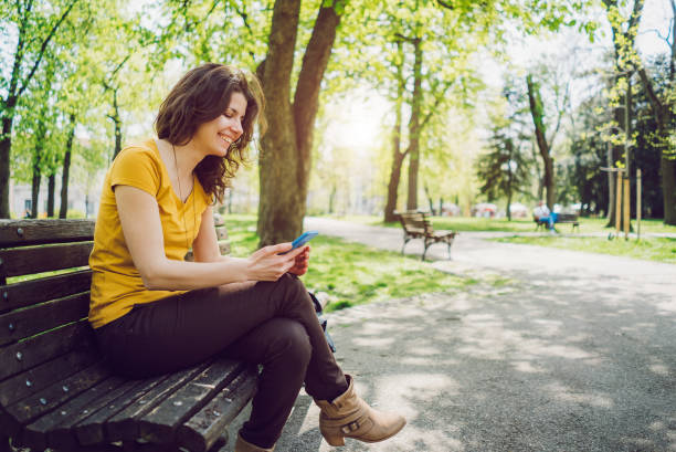 Using phone in a park stock photo