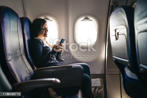 Young woman is using phone on an airplane ride