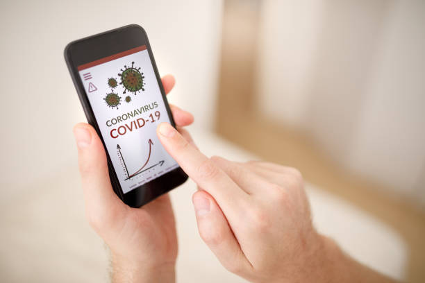 Using phone to stay informed about covid-19 stock photo