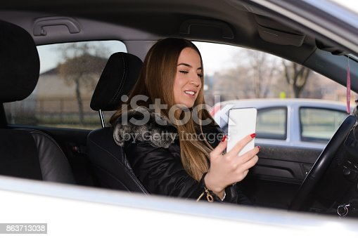 607592606 istock photo Using phone while driving 863713038
