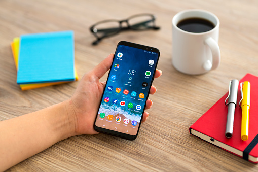 İstanbul, Turkey - February 2, 2019: Hand holding a smart phone on a wooden desk. The smart phone is an Samsung Galaxy S9 plus. Samsung Galaxy is a touchscreen smart phone produced by Samsung Electronics.