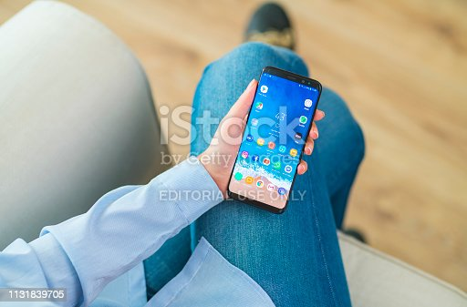 İstanbul, Turkey - February 4, 2019: Woman using smart phone on a couch. The smart phone is an Samsung Galaxy S9 plus. Samsung Galaxy is a touchscreen smart phone produced by Samsung Electronics.