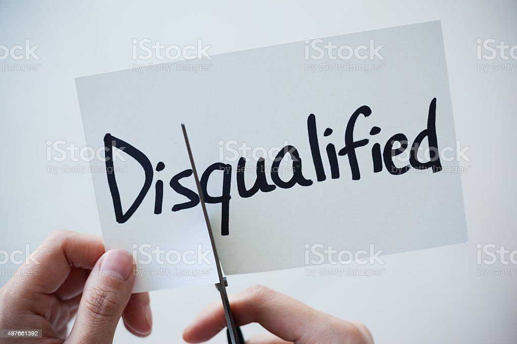 Using Scissors Cut the Word on Paper Disqualified Become Qualified stock photo