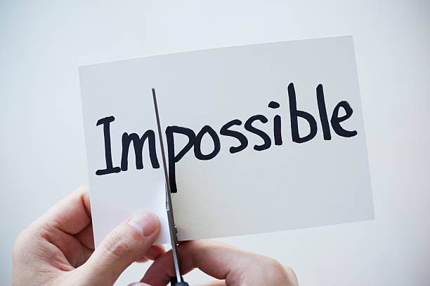 using scissors cut the word on paper impossible become possible - possible stock photos and pictures