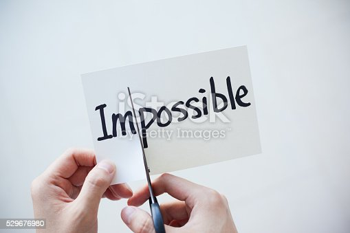 Close-up of hand using scissors cutting the word on paper, Impossible become Possible.