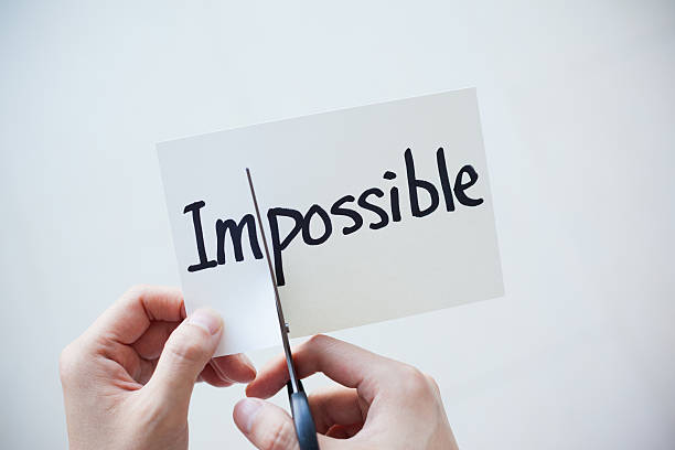 Using Scissors Cut the Word on Paper Impossible Become Possible stock photo