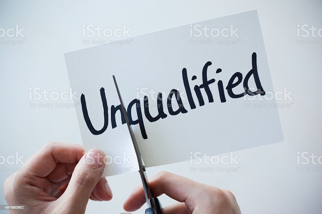 Using Scissors Cut the Word on Paper Unqualified Become Qualified stock photo