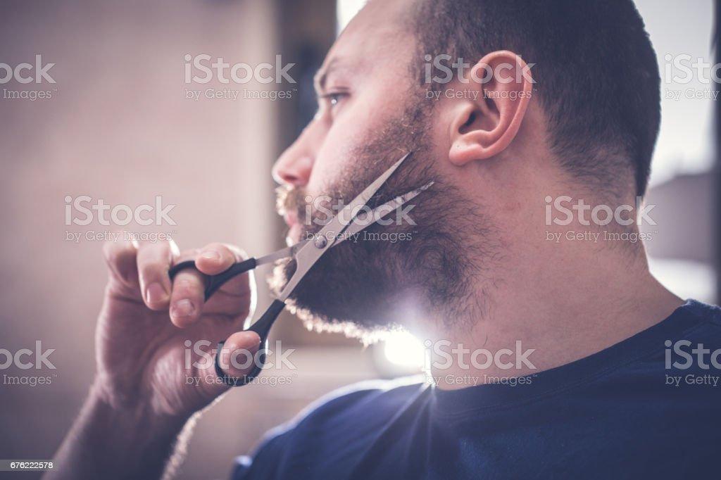 One man, using scissors for his beard indoors.