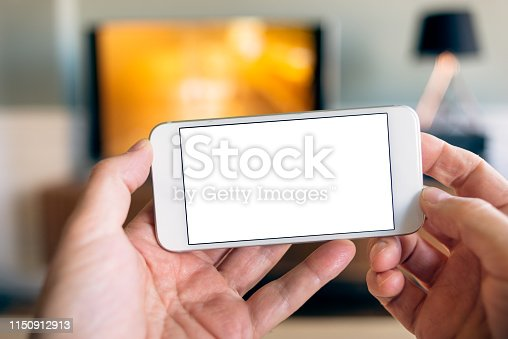 Home Multimedia - User point of view (POV) holding up a smart phone, interacting with TV in the background. The mobile phone has a blank white screen to drop-in your graphic.