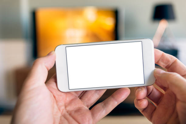 POV Using Smart Phone App at Home with TV stock photo