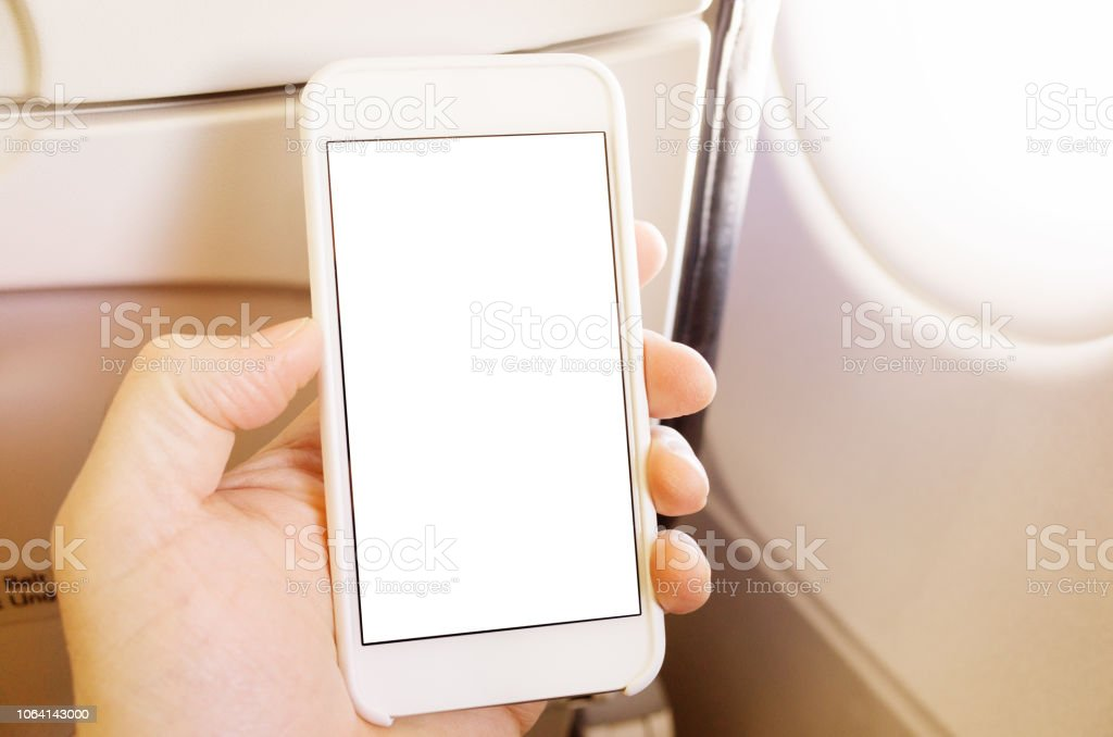 Using Smart Phone App in Airplane stock photo