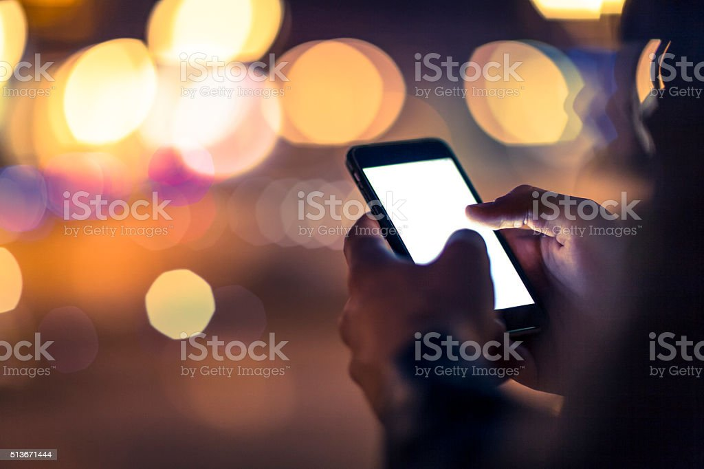 Using smart phone at nighttime outdoors stock photo