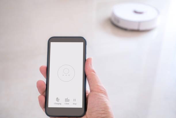 using smart phone control the robotic vacuum cleaner stock photo