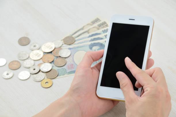 mit smartphone während geld bezahlen - gebühr stock-fotos und bilder