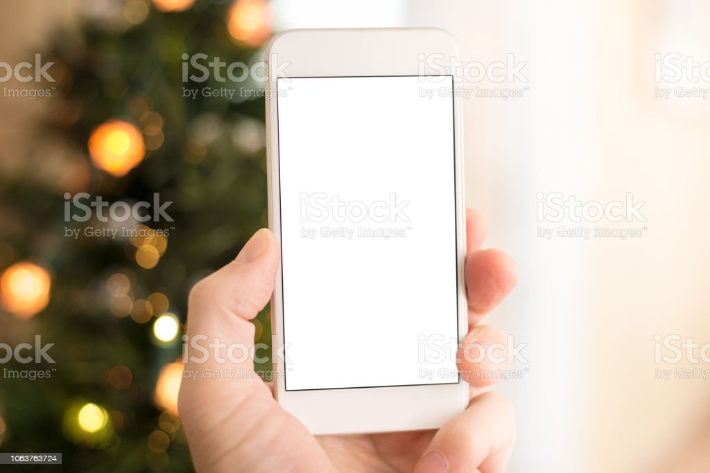 Using Smart Phone with Blank Screen POV at Christmas stock photo