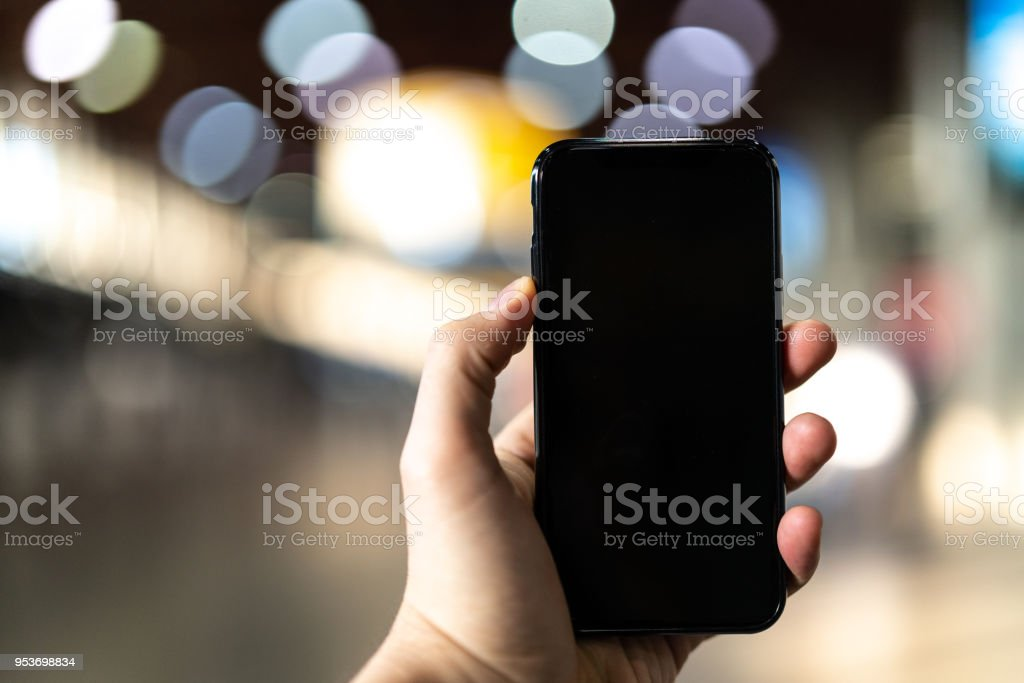 Using Smart Phone with Blank Screen POV in with Bokeh Background stock photo