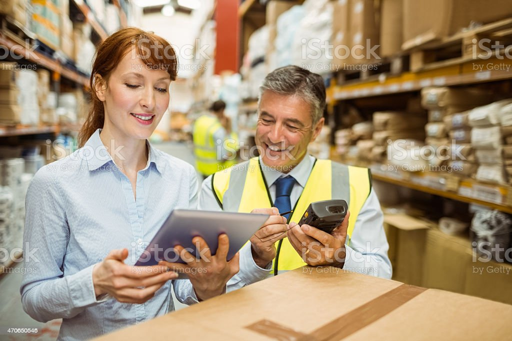 Using smart tablets to manage in a warehouse environment stock photo