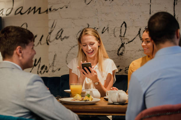using smartphone in a restaurant - eating technology stock photos and pictures