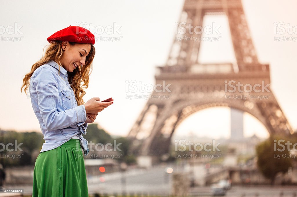 Using smartphone in front of the Eiffel Tower stock photo