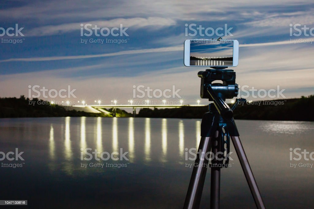 Using smartphone like professional camera on tripod to capturing night landscape stock photo