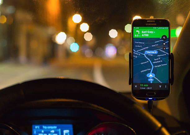 usando teléfono inteligente sistema de navegación satelital por la noche para obtener indicaciones para llegar. - sistema de posicionamiento global fotografías e imágenes de stock