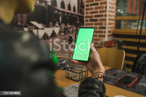 istock using smartphone with green screen in coffee shop 1251304862