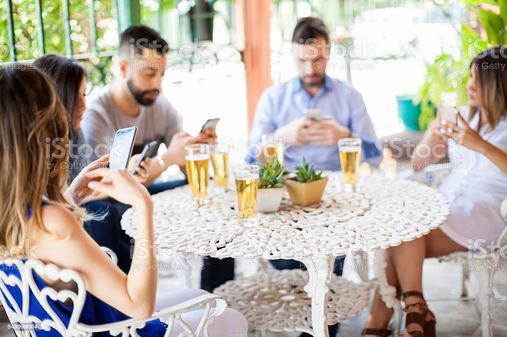 Using smartphones during a friend reunion stock photo