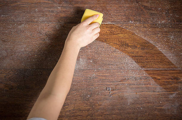 Using sponge for cleaning dusty wood stock photo