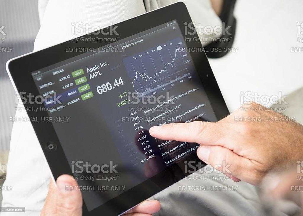 Using stock market app with ipad 3 stock photo