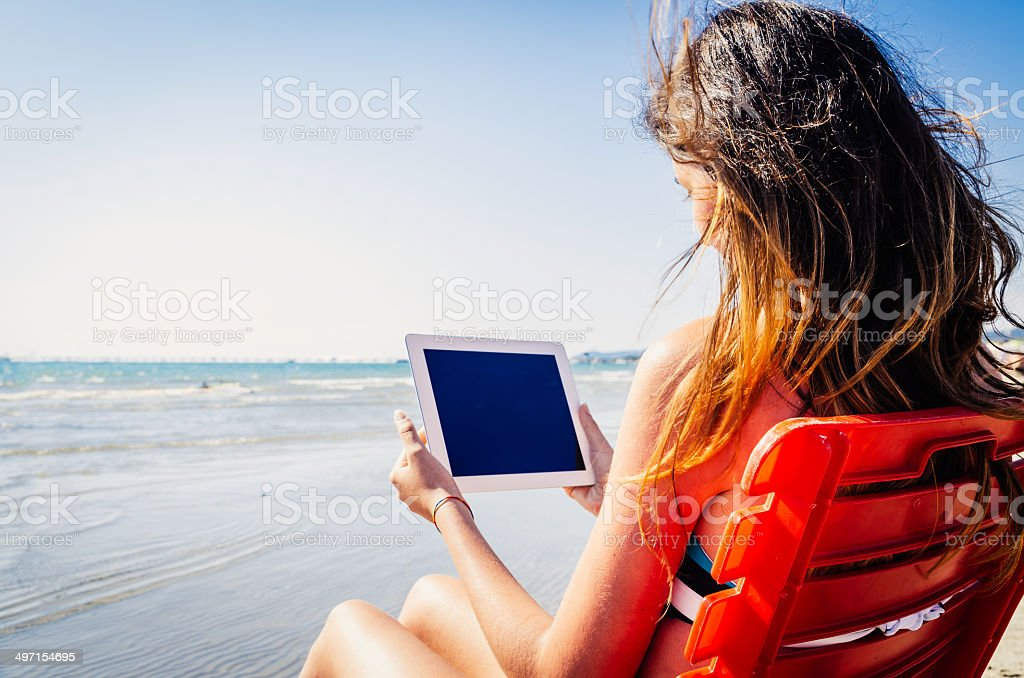Using tablet at the beach stock photo