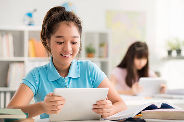 Using tablet in class Smiling Asian schoolgirl using digital tablet in the class vietnamese ethnicity stock pictures, royalty-free photos & images