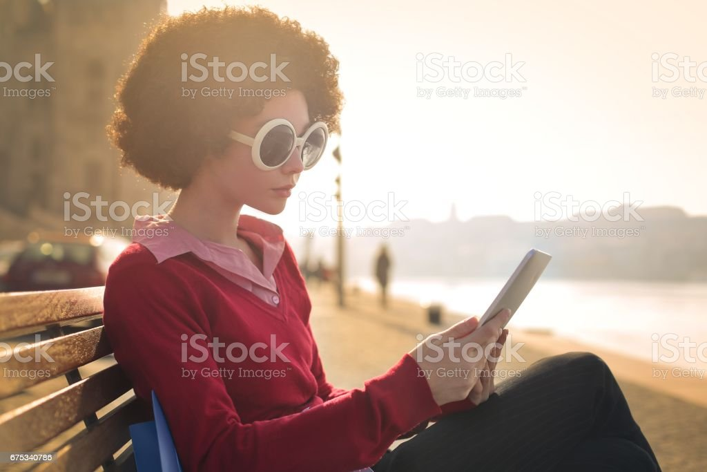 Using tablet next to the river stock photo