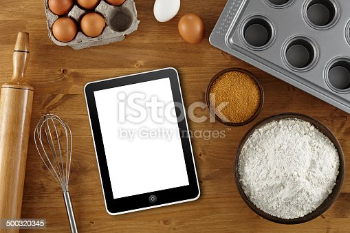 Directly above view of a wood table with pastry ingredients. Clipping path on tablet pc screen.