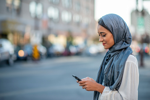 A Muslim woman is outdoors on a sunny day. She is wearing casual clothing and a head scarf. She is standing near a road and sending a message with her smartphone.