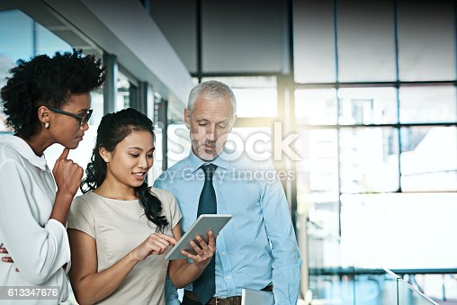 Shot of a business team using a digital tablet while having an informal meeting