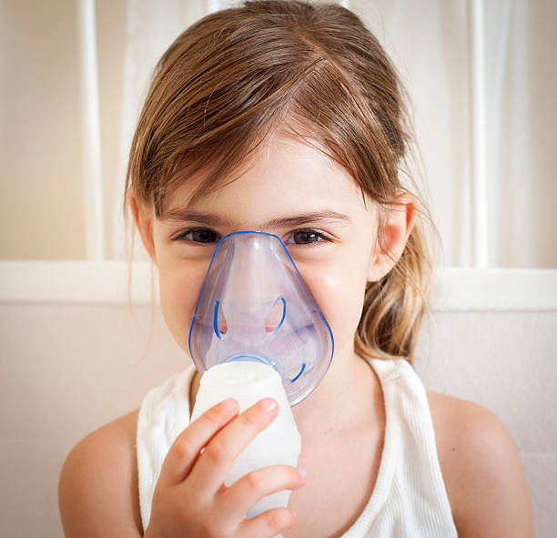 "Using the inhalation mask ""Young little girl using nebuliser to relieve the cough. Square framing, shallow depth of field, adobeRGB photo. Vignette added in postprocess."" smoke inhalation stock pictures, royalty-free photos & images"
