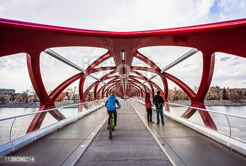 Calgary, Canada - A cyclist and pedestrians on the Peace Bridge across the Bow River in Calgary. The bridge was designed by Santiago Calatrava.