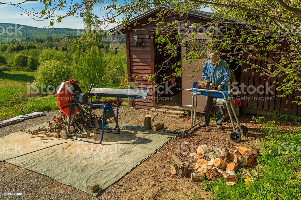 using the splitter to split a log into firewood stock photo